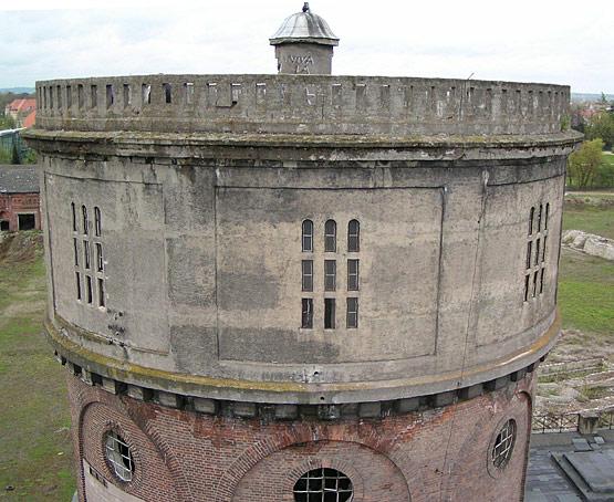 """Abb. 2: Wasserturm """"Kavalier Dallwigk"""" in Ingolstadt, erbaut 1916-17, vor der Instandsetzung. Der Sichtbeton zeigt, neben Moos- und Algenbewuchs, eine Vielzahl von Betonschäden, wie z. B. Rissbildungen als Folge von Zwang sowie Kantenabbrüche und Abplatzungen als Folge von Frost und korrodierender Bewehrung"""